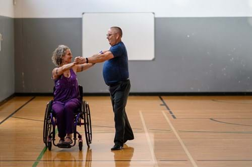 Lady in wheelchair dancing with man